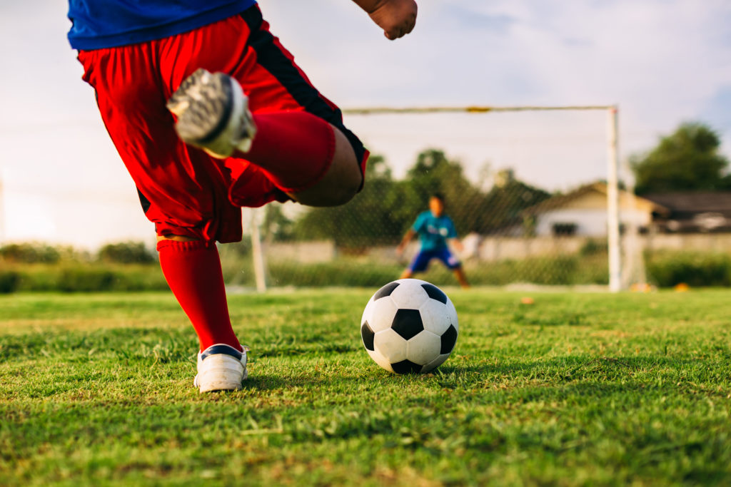 Young boy kicking football