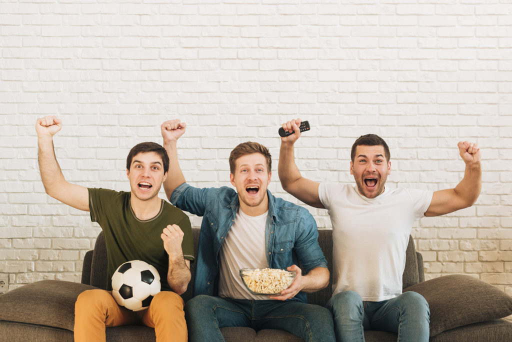 Guys cheering over football match