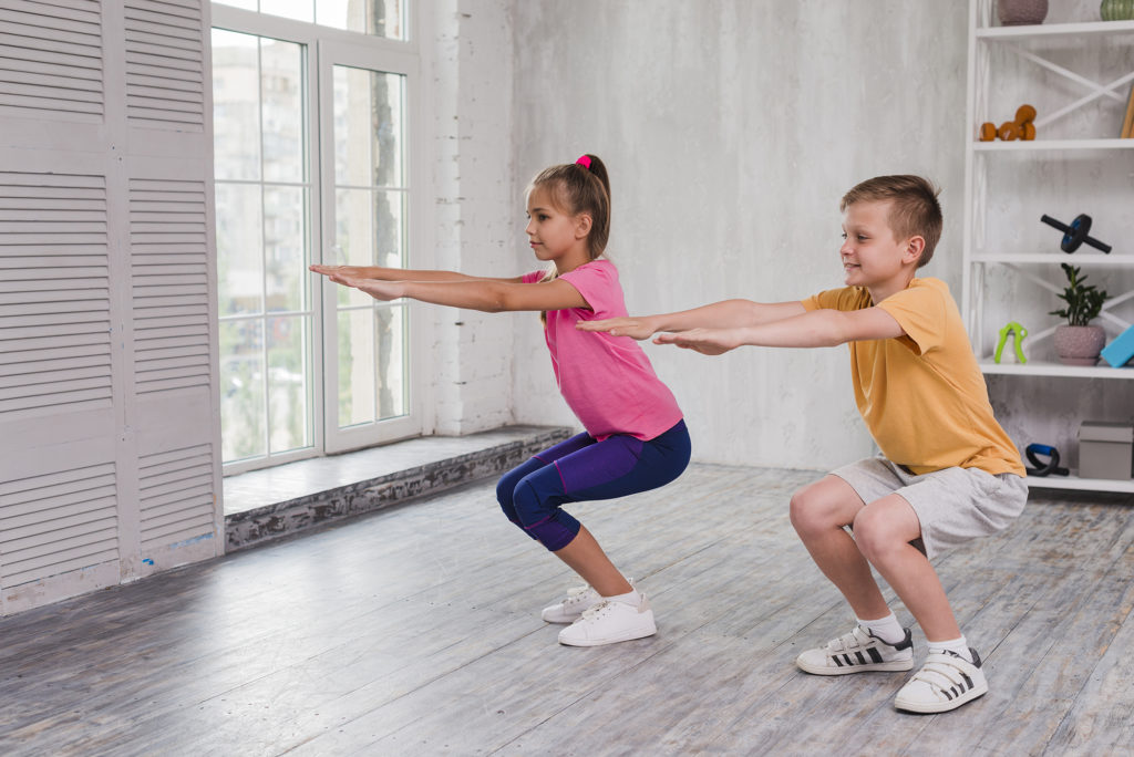 Two children exercising at home