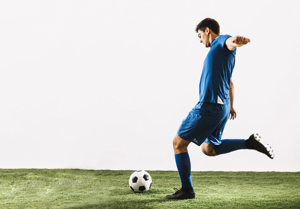 Man kicking football