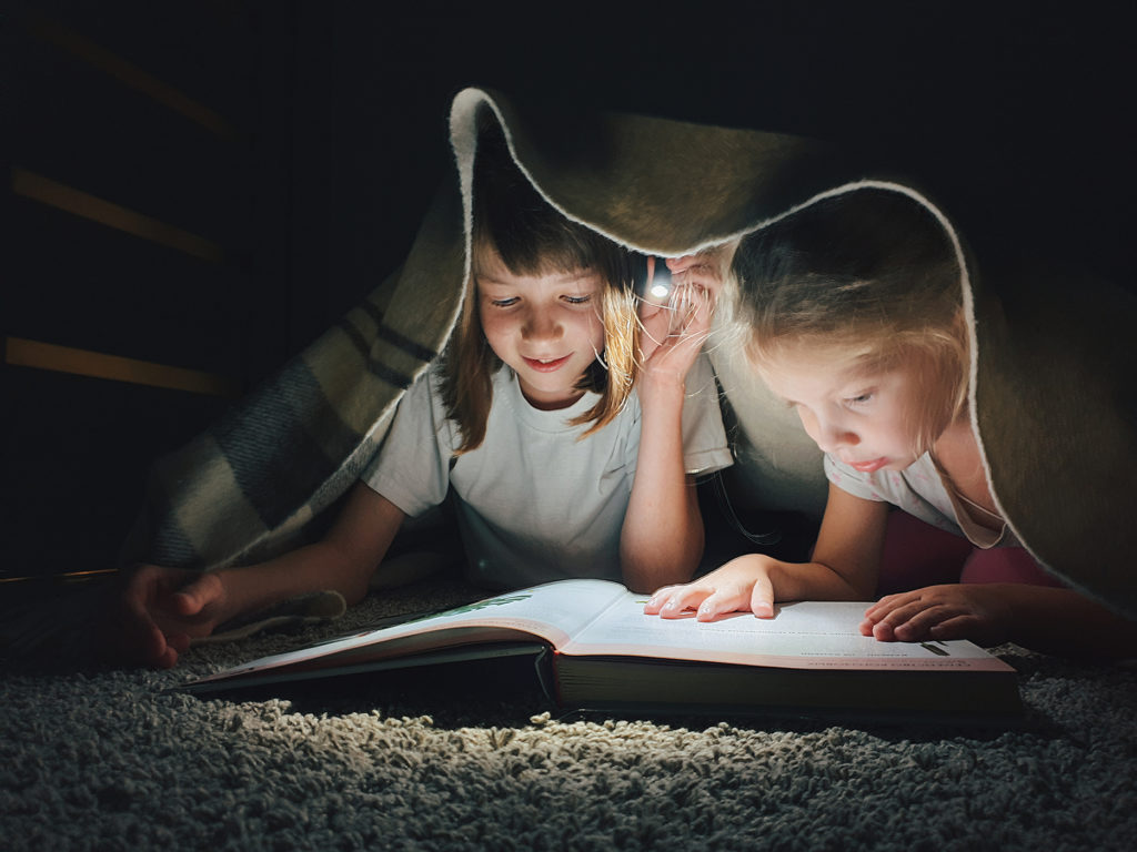 Young girls reading under the covers
