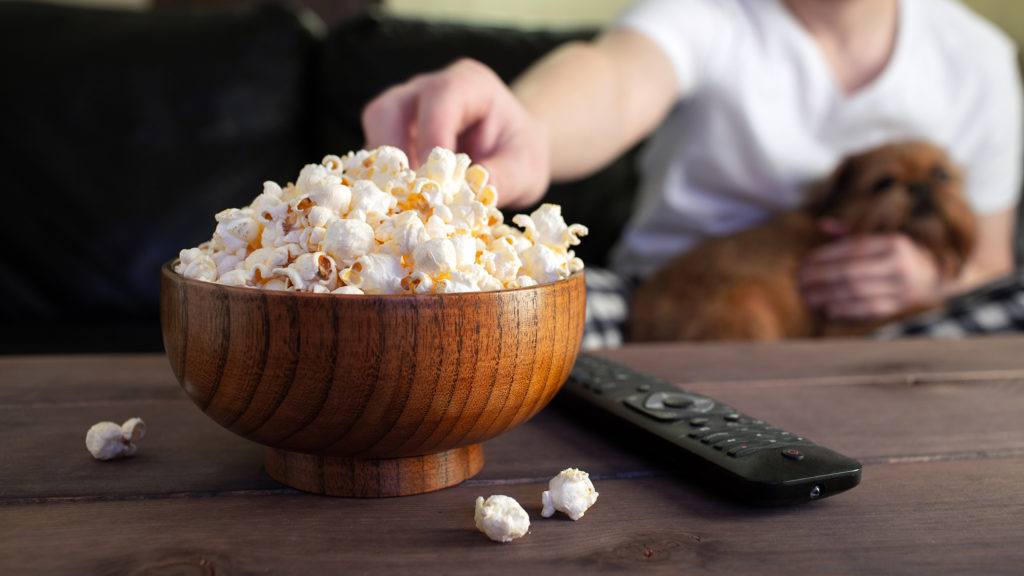 Reaching for popcorn in a wooden bowl
