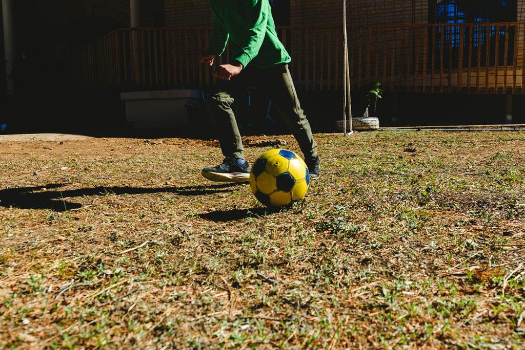 Boy kicking a football in his back garden