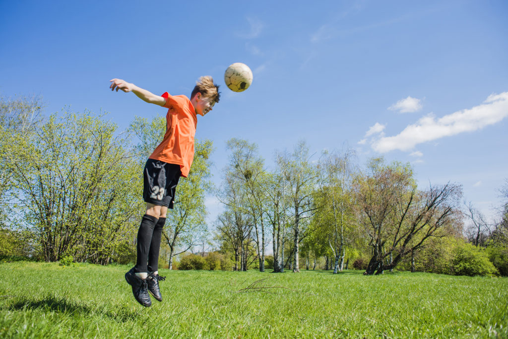 Young football player heading a football