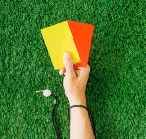Football referee holding a red and yellow card